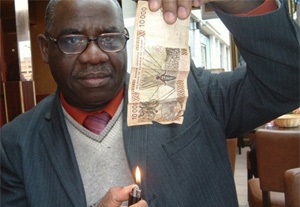 Nicolas Agbohou s'apprête à brûler un billet de banque en franc CFA. D. R.