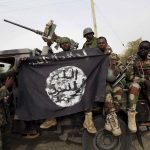 Des soldats de l'armée nigérienne tiennent un drapeau du groupe terroriste Boko Haram. D. R.