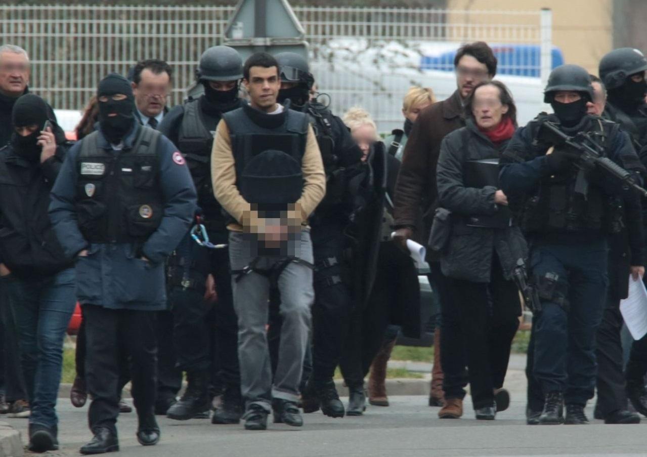 Sid Ahmed Ghlam menotté et encadré par les forces de police lors d'une reconstitution. D. R.